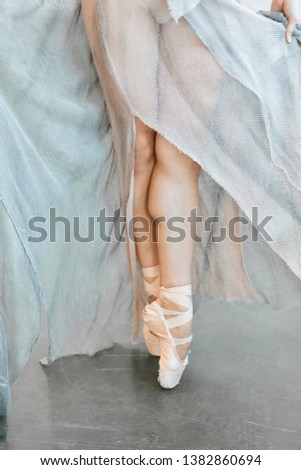 Strong professional ballet dancer feet standing on toes in studio close up. Ballerina dressed in long airy flowing clothes for performance