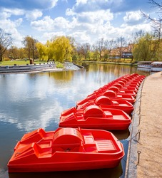 Strong red colour pedal boat in centre of city Odense by the Odense river. The area, called Munkemose, is dedicated to relaxing and picnic.