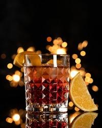 Strong refreshing drink with orange. Golden alcoholic shot against of sparklers backlit on black background. Holiday event concept. Vertical format. Copy space.