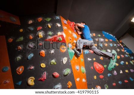 strong rock climber practicing...