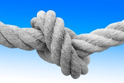Strong rope with single knot - concept image against a blue and white background.