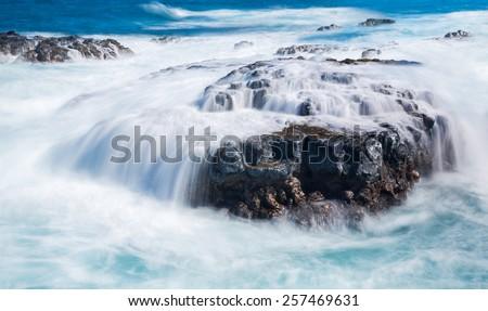 Strong sea waves flow over lava rocks on edge of the shore near Queens Bath, Kauai, Hawaii