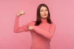 Strong self confident brunette woman in pink sweater showing her arm muscles raising hand, free and independent, emancipation. Indoor studio shot isolated on pink background