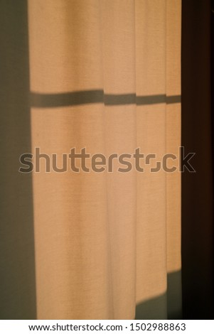 Strong shadows fall on curtains at sunset light. Modern minimal design in beige. Minimalism concept interior room in home, hotel or office