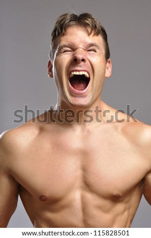 Strong shirtless man screams while he flexes muscles