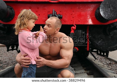 strong shirtless man sits on railroad with little girl, how old are you?