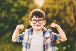 Strong, smart and funny little boy playing outdoors, wearing eyeglasses and blue plaid shirt