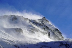 strong south wind in the alps in winter on a sunny day in the national park hohe tauern in austria