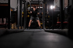Strong sportsman doing battle rope exercise at cross fit gym, having intense training alone. Concentrated caucasian man doing cross fit exercise while working out in gym, in sportswear