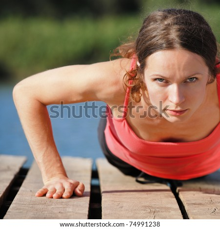Strong sporty female doing push-ups outdoors