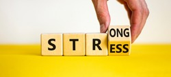 Strong stress symbol. Businessman turns wooden cubes with words 'strong stress'. Beautiful yellow table, white background, copy space. Business and strong stress concept.