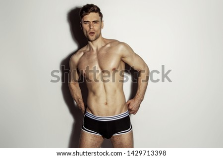 Strong stripped muscle male model in black underwear with white strips on white isolated font background with shadow #1429713398