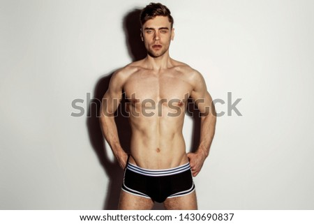 Strong stripped muscle male model in black underwear with white strips on white isolated font background with shadow #1430690837