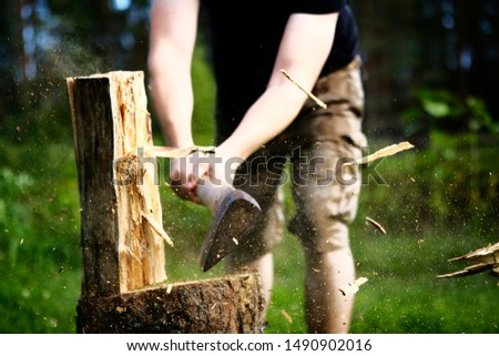 Strong strong man in protective pants splits with an ax log. Slivers of dust fly. Logging firewood. sunny day
