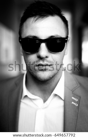 Strong stylish successful man in a suit and glasses. Men's look. Black and white brutal man portrait. Businessman. Guy in suit and glasses posing on camera.Stylish men's glasses. #649657792