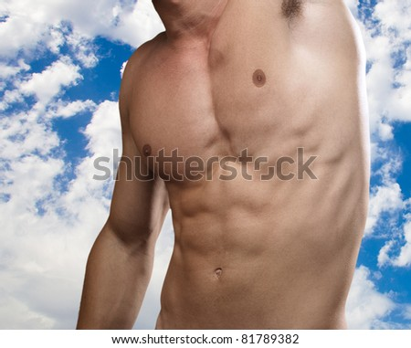 strong torso of young man with a cloudy sky as a background