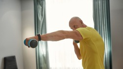 Strong trainer with dumbbells in hand working out at home. Male trainer boxing with a dumbbell in his hands. Man in sportswear standing in a boxer stance and training