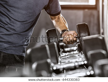 Strong well built bodybuilder lifting dumbbell weights getting ready for exercise in fitness #644330383