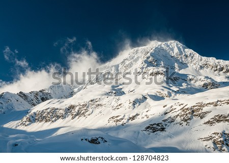 Strong wind blows snow away from a highlighted mountain peak