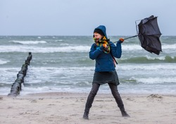 strong wind destroys a woman's umbrella during a beach walk