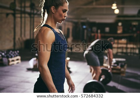 Strong woman and man doing preparations for deadlift. Horizontal indoors shot
