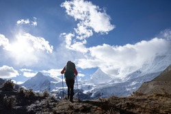 Strong woman backpacker hiking in winter high altitude mountains