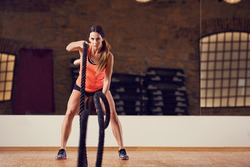 Strong woman doing battle rope exercise at gym