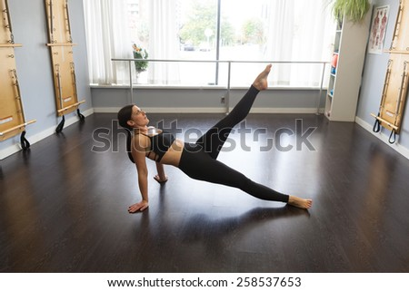 Strong woman doing Pilates floor exercises