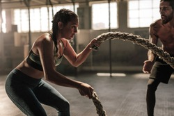 Strong woman exercising with battle ropes at the gym with male trainer. Athlete doing battle rope workout at gym with instructor.
