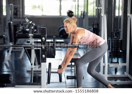 Strong woman exercising with iron barbell weight plate in a fitness club, doing exercises in gym