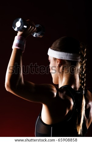 strong woman lifting up barbells.Shot in studio on a red background.