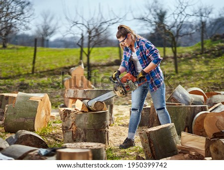 Strong woman lumberjack cutting big logs with her chainsaw Stock photo ©