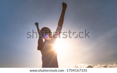 Strong woman overcoming adversity. Woman with fist up to the sky. People power and strength concept.  Stock photo ©