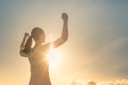 Strong woman, Winning, success , and life goals concept. Young woman with arms flexed facing the sunset.