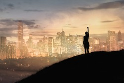 Strong woman with fist in the air standing on top a mountain overlooking the city. Triumph, victory and feeling determined.