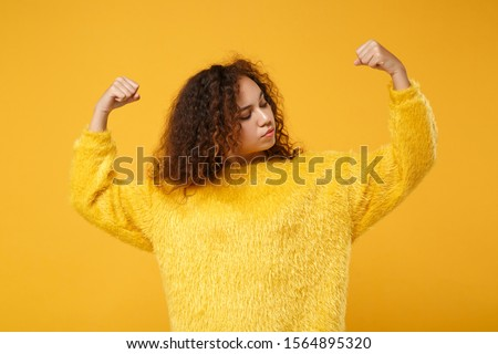 Strong young african american girl in fur sweater posing isolated on yellow orange background, studio portrait. People sincere emotions lifestyle concept. Mock up copy space. Showing biceps, muscles Stock foto ©