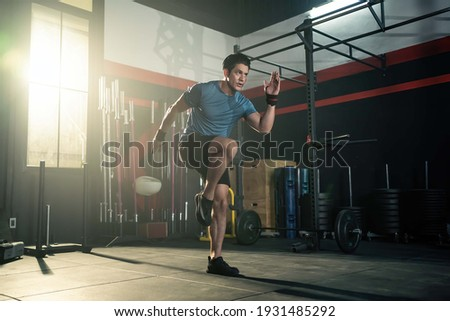 Strong young athlete fit man running in fitness gym. The man with sportswear showing his strength muscular in body. Bodybuilding exercise and sport workout training concept.
