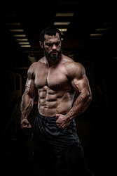 strong young bearded athlete male with perfect sport physique body torso muscle in dark fitness gym