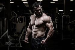 strong young bearded caucasian male with sport physique body standing in dark fitness gym with equipment