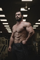 strong young bearded caucasian man with perfect sport physique body in dark fitness gym