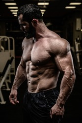 strong young bearded caucasian man with sport physique body torso standing in dark fitness gym with equipment
