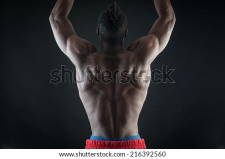 Strong young black man shirtless portrait against black background. Back view.