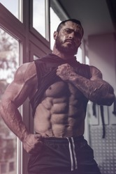 strong young caucasian man athlete with beard showing his perfect physique abdominal muscle near window in sport gym