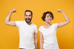 Strong young couple friends bearded guy girl in white empty blank t-shirts posing isolated on yellow orange background in studio. People lifestyle concept. Mock up copy space. Showing biceps, muscles