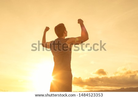 Strong young man flexing his arms to the sunset sky. People victory and inner strength concept.