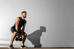 Strong young muscular focused fit man with big muscles holding heavy kettlebells