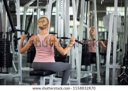 Strong young woman exercising with pulldown machine in a fitness club, doing exercises in gym