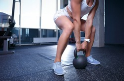 Strong young woman lifting weight with kettlebell in gym club.Girl bodybuilder doing deadlift exercise with kettle bell sports tool in fitness studio.Female strength and health concept.Train your body