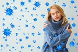 Stronger immunity - better disease resistance. Young woman wearing warm blue sweater surrounded by viruses on light background