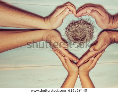Strongly holding hands of a family making a heart sign on wooden background. Family bonds, protection, security, hope, faith, solidarity.